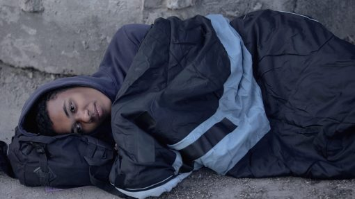 Desperate black man lying street covered with sleeping bag, poverty hopelessness